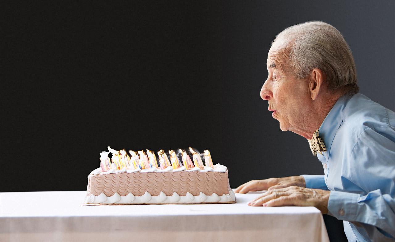 Old man retired blowing out birthday candles