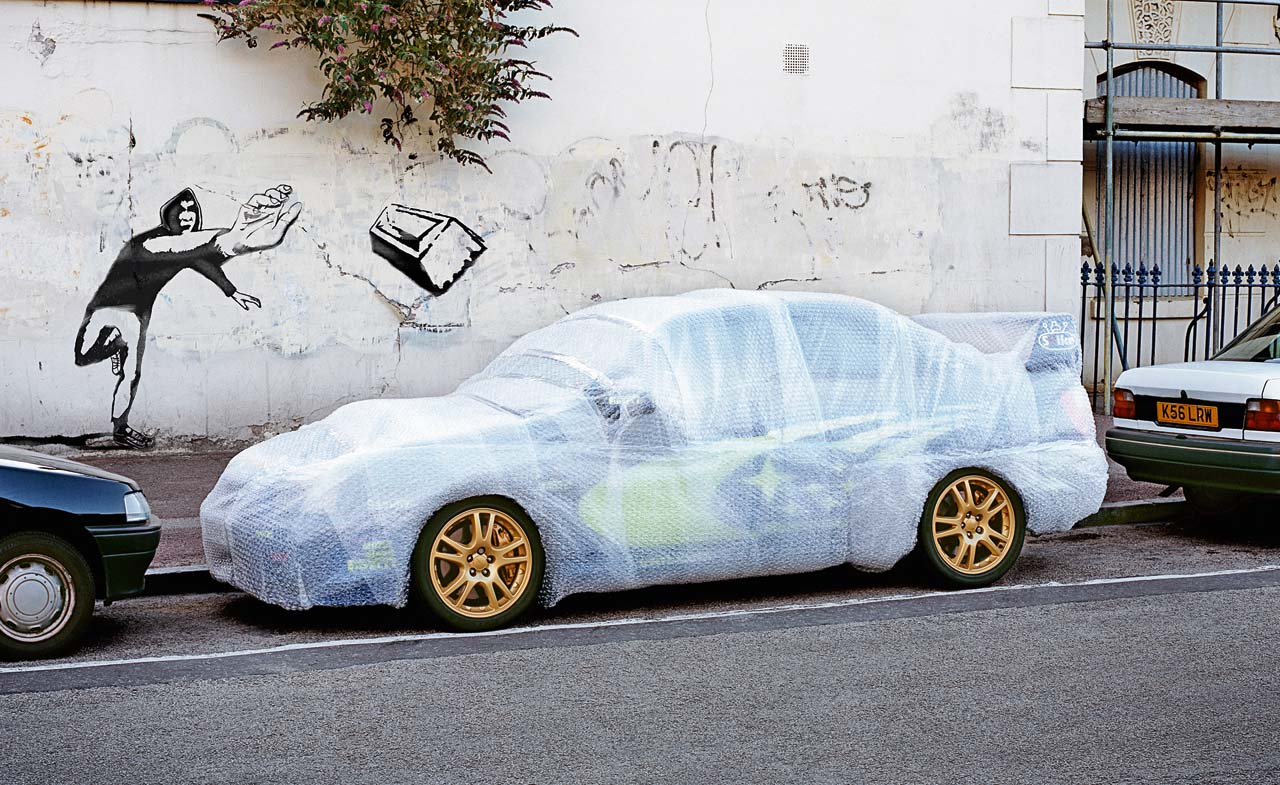 Grafitti Throwing Brick At Bubble Wrapped Car