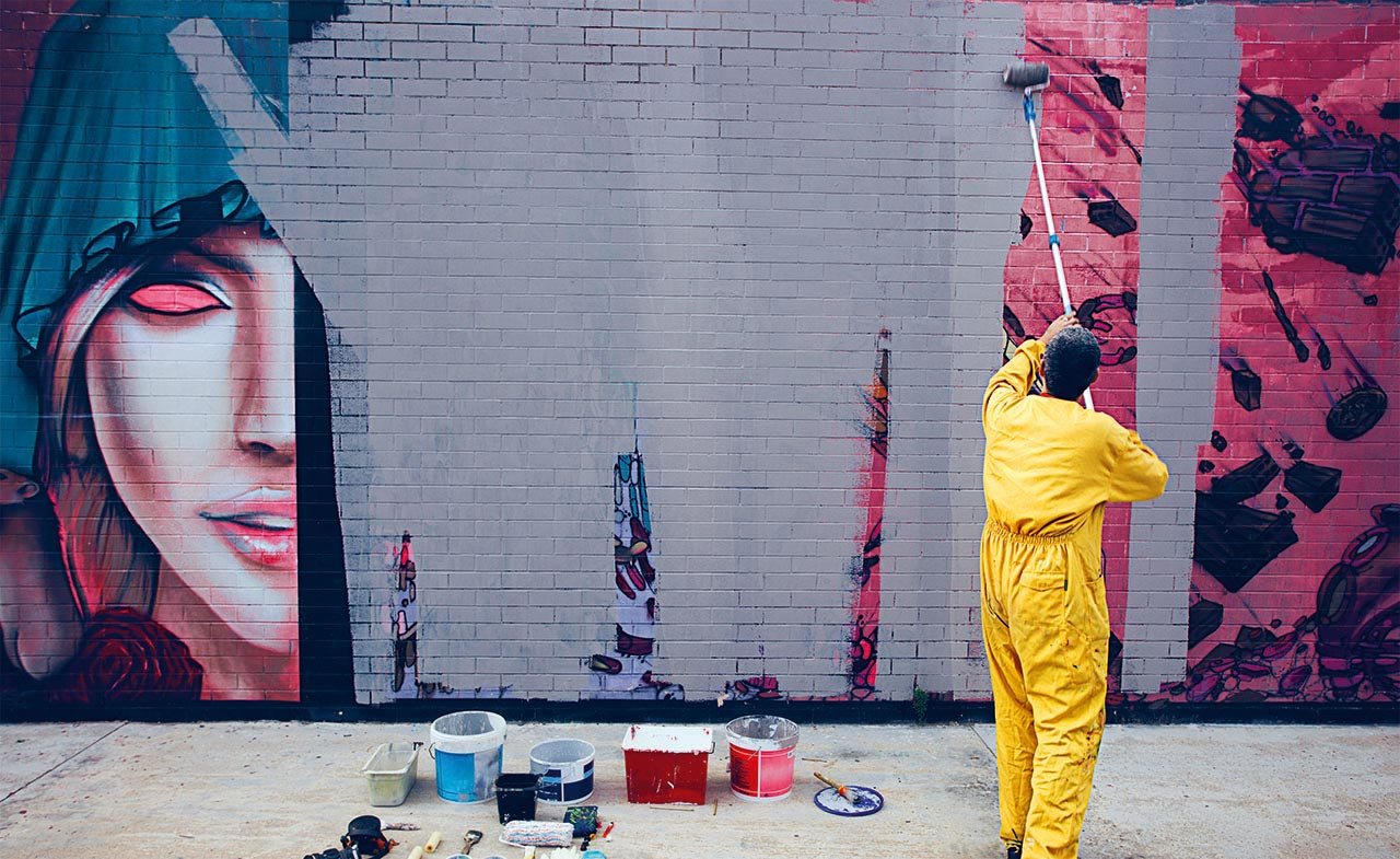 Man paints over grafitti
